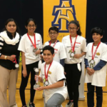FIRST LEGO League team, the Space Invaders, show their medals