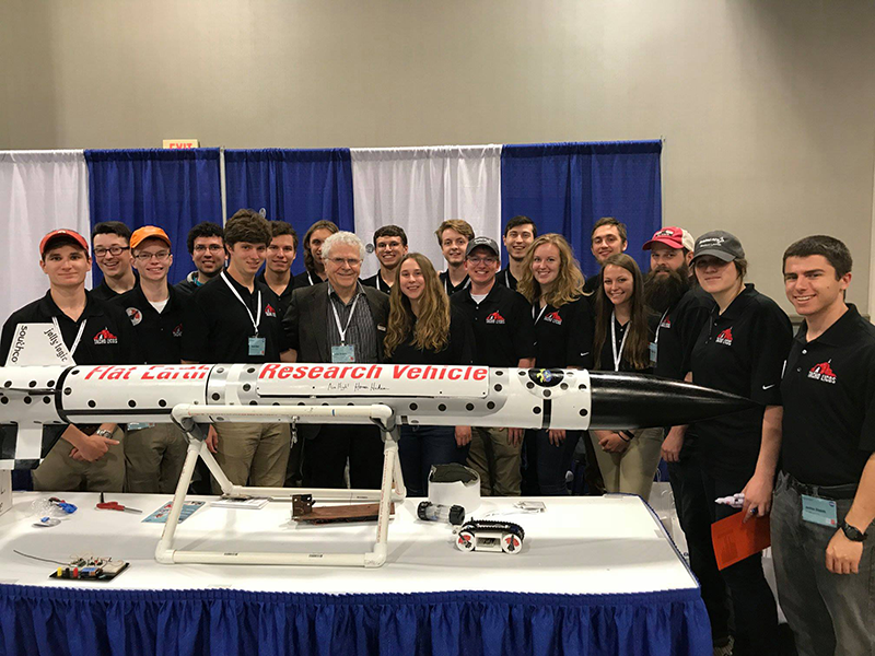 Homer Hickam, author of Rocket Boys and inspiration for the film October Sky, visits the NC State high-powered rocketry team's booth at the 2018 NASA competition. Lauer stands second from the right from Hickam.