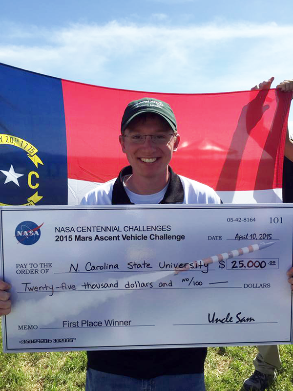 Lauer holds up the check from the high-powered rocketry team's big win at the 2015 NASA Centennial Challenge competition.
