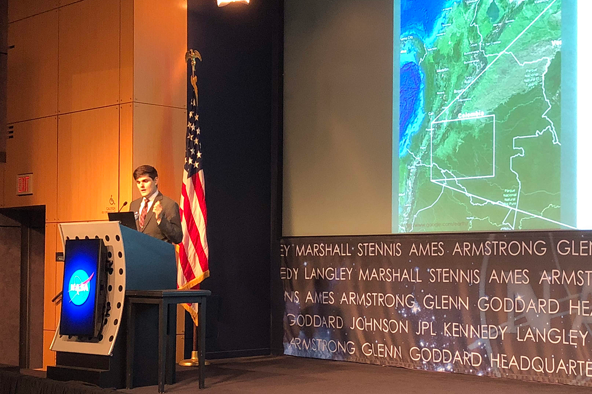Theurer delivers a presentation about his NASA DEVELOP internship work studying deforestation in Colombia with satellite images onstage at a showcase.