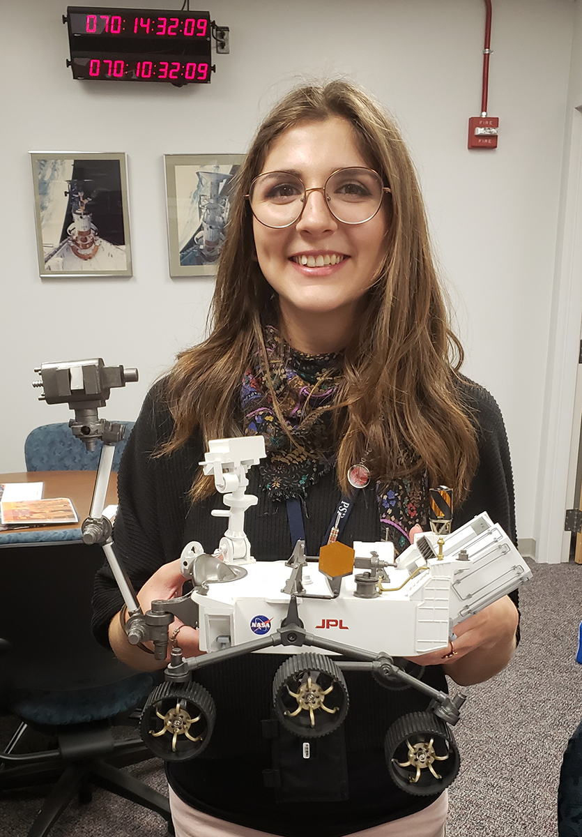 Stephanie Smith holds a scale replica of the NASA Mars 2020 mission's Perseverance rover. Smith's company, United Launch Alliance (ULA), provided the rocket that launched the rover on its mission on July 30, 2020. Smith and her team ensured the rocket and payload were free of contaminants before launch.