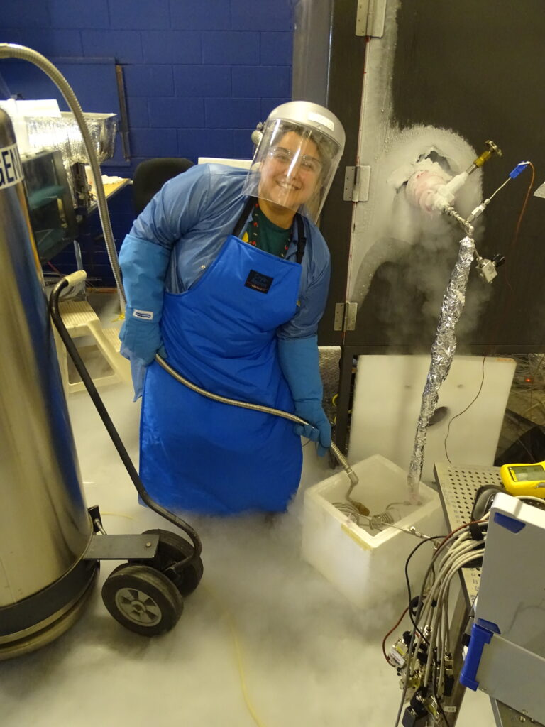 Adams fills a container with liquid nitrogen, which covers her feet and legs with vapor.