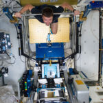 An astronaut uses the ARED machine on the International Space Station.