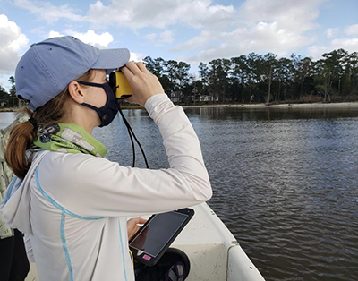 Jessica Richter measures the distance from vessel to shore using a laser rangefinder, to verify the location of survey coordinates along the shoreline of the Neuse River Estuary.